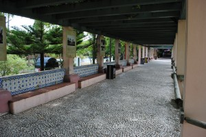 A long stretch of Portuguese pavement under a pergola
