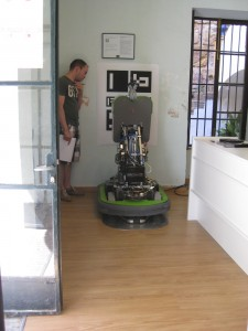 FROG robot on its stainless steel docking station, surrounded by wood laminate floor