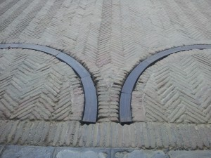 transition from patterned cobblestones in concrete over row of stone flags onto herringbone pattern laid brick with deep-set gate wheel tracks with wooden fillers