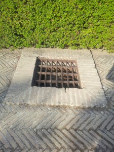 drain grate in raised brick surround along herringbone laid brick path