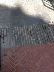 transition from herringbone laid red bricks in concrete, over dark red bricks laid in line in concrete, to flagstones and chequer flagstones / cobbles in concrete