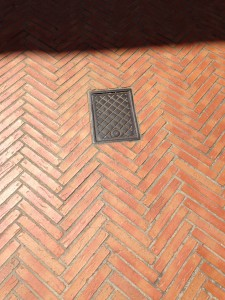drain cover set in smooth red bricks herringbone laid