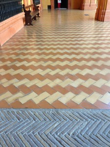 transition from yellow brick, herringbone laid in concrete, to glazed tiles, herringbone laid