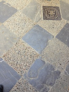 chequer: flagstones/cobbles in concrete with inset drain cover